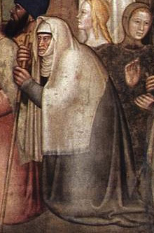 Elderly lady in a veil that covers her to mid back. she is also wearing a wrapped veil underneath.