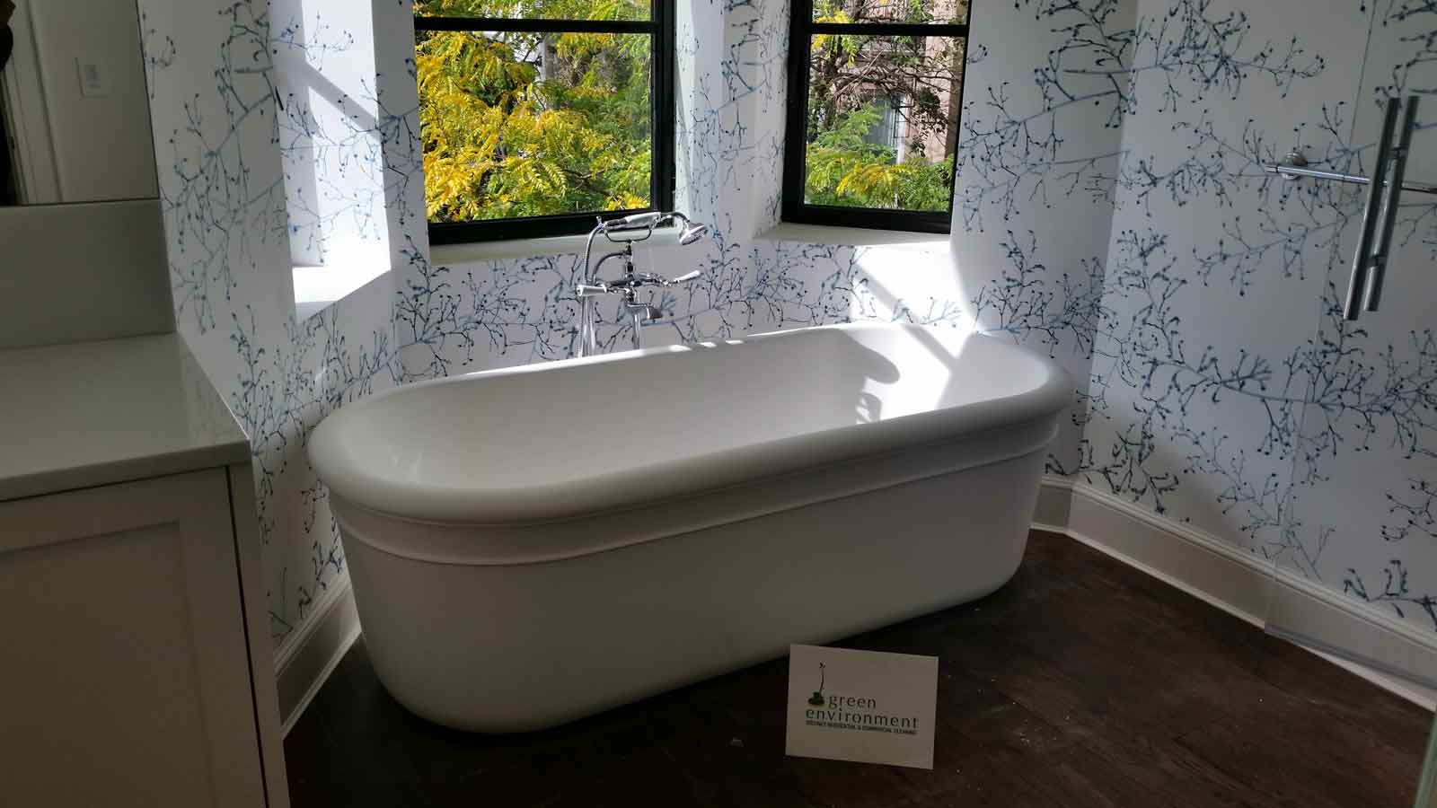 Tub surrounded with vine wallpaper and windows.