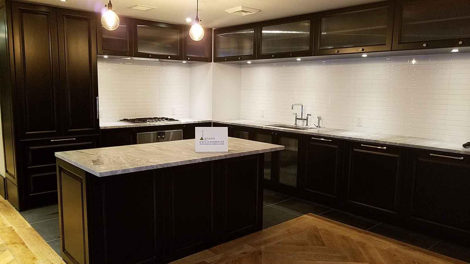 Kitchen with slate floor and dark wood custom cabinets.