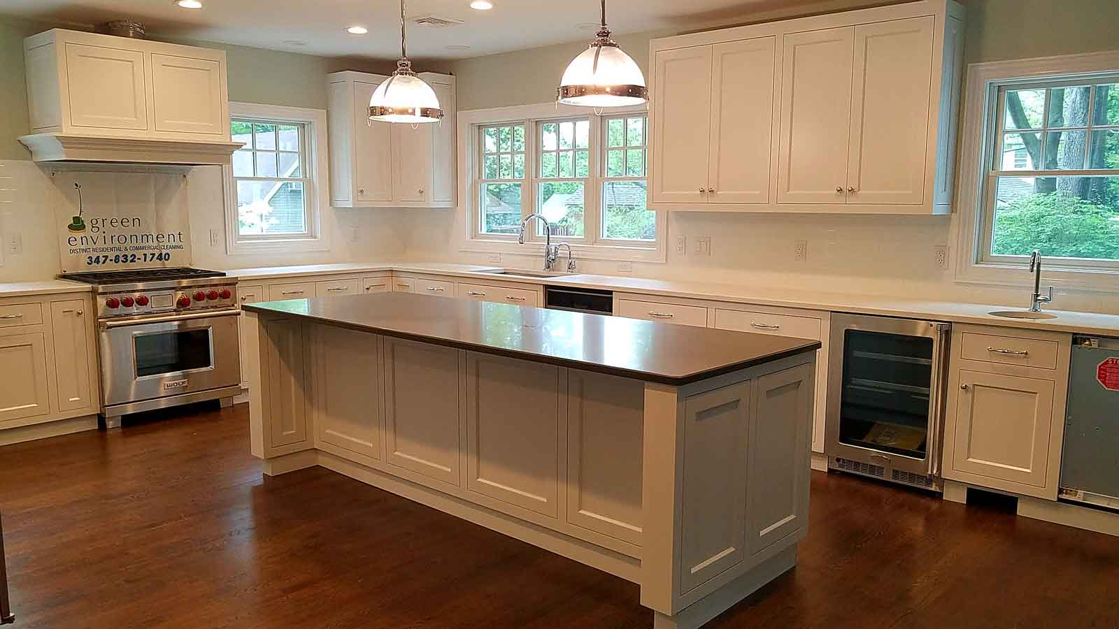 Luxury kitchen with two sinks, windows, and custom cabinets.