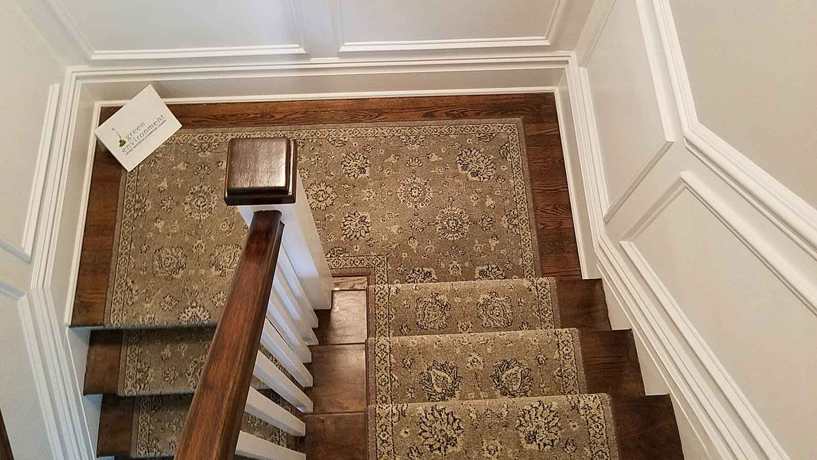 Wooden stairwell with carpet runner after a post-construction cleaning.