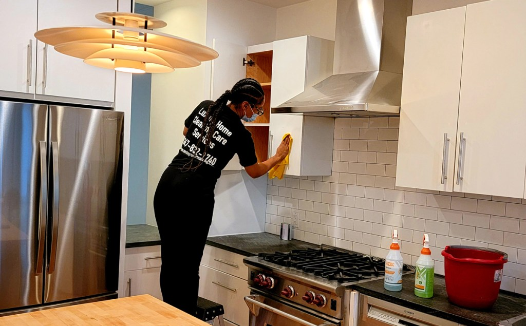 Home cleaning specialist deep conducting a monthly general cleaning in a kitchen for a Post Green Cleaning client.