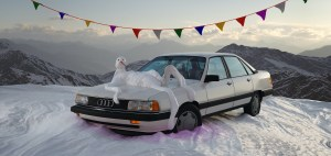 An audi sits on a snowy mountain with a melting snowman laying on top of the hood. A banner of colorful flags hangs from the top.