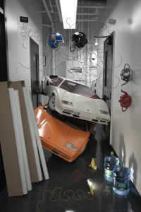 One white countach piled on top of an orange countach in a hallway.