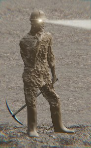 Man covered in mud standing in gravel holding a pickaxe.