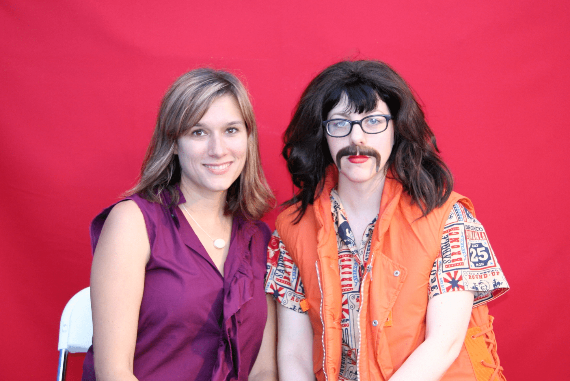 Jennifer McCoy and a woman dressed as Kevin McCoy sit in front of a red background.