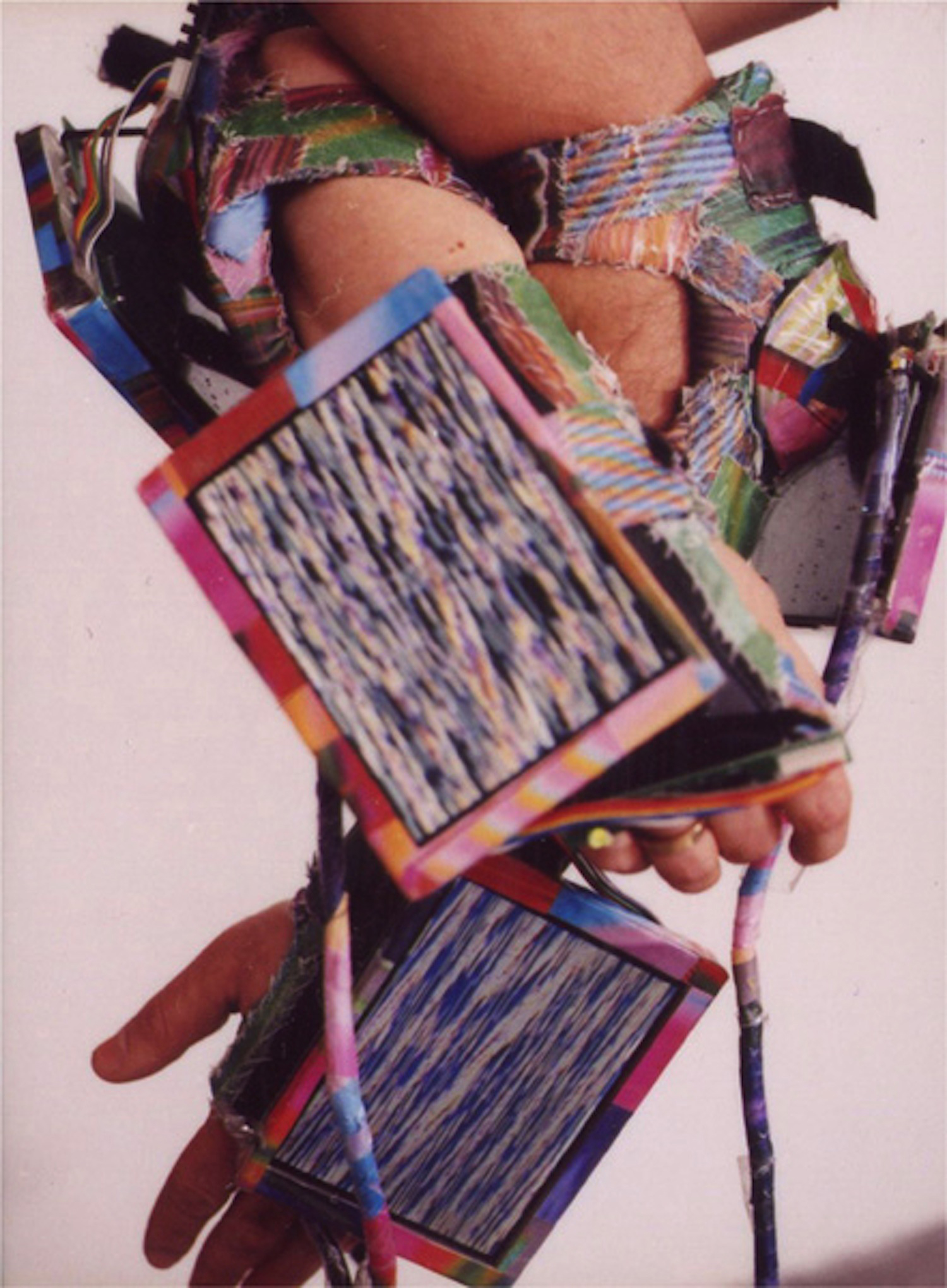 Hands bound together by fabric cuffs with screens dangling on each end.