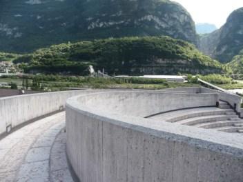 Dalla cima del percorso che avvolge la chiesa, compare la diga del Vajont
