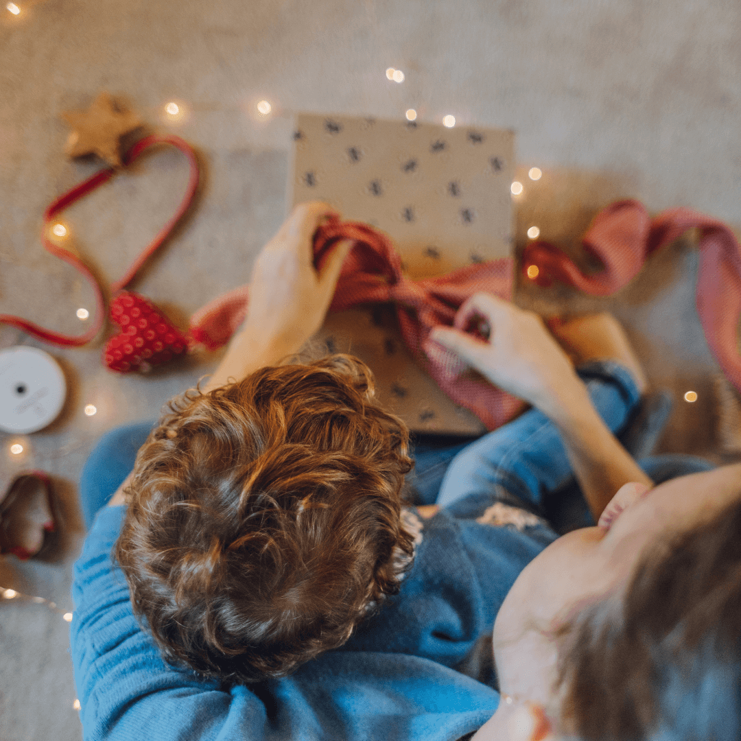 mother wraps christmas gifts with her child