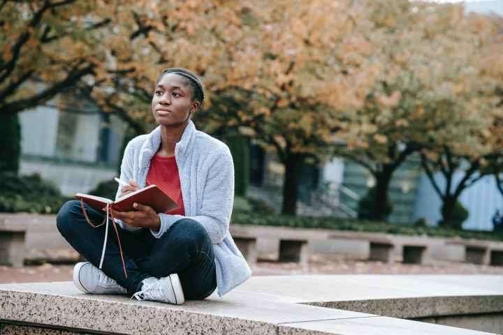 dreamy black student with diary in urban park