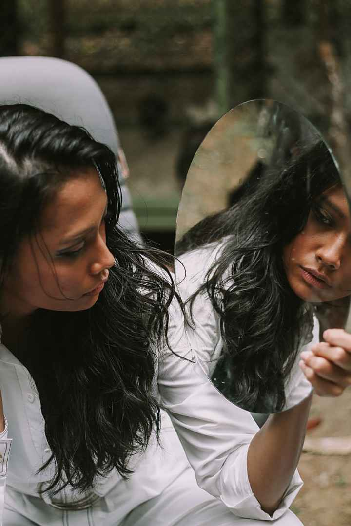 photo of woman holding and looking at a mirror