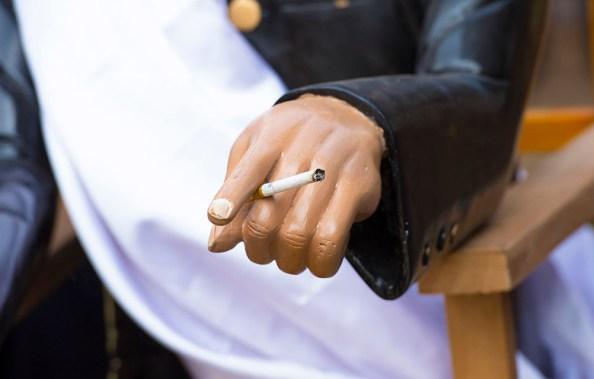 A smouldering cigarette in the hand of a modern tau-tau