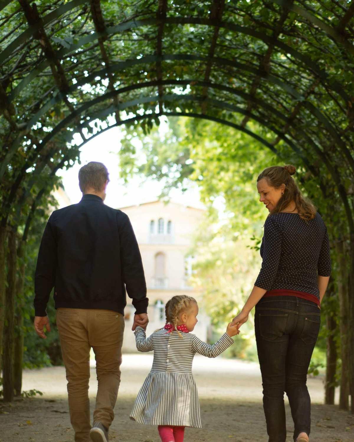 Familie mit Kind in der Mitte von hinten in Laubengang