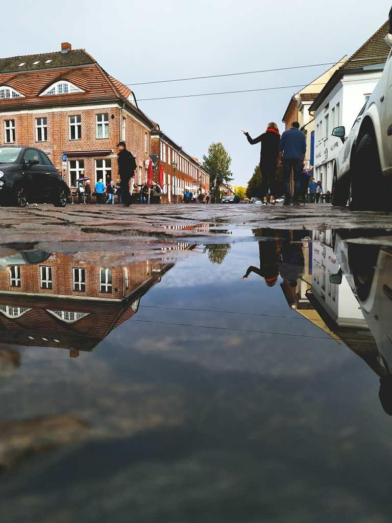 Häuser spiegeln sich in Pfütze auf der Straße