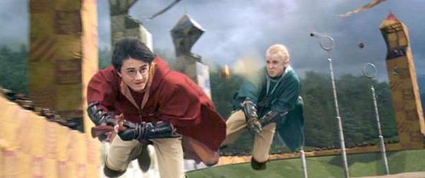 Harry Potter v červeném famfrpálovém hábitu a Draco Malfoy v zeleném famfrpálovém hábitu se snaží chytit Zlatonku.