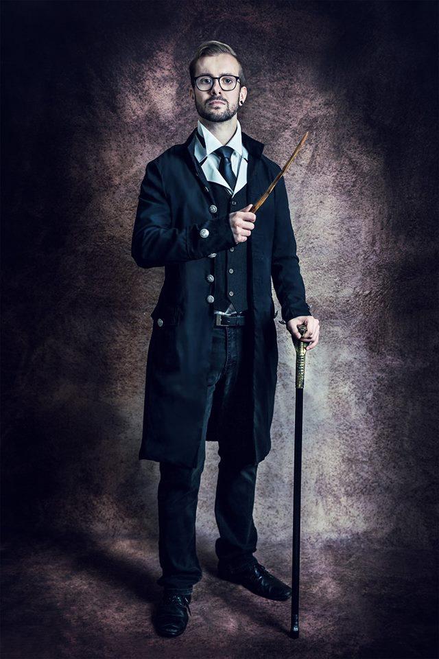 Promo fotka profesora Votočka z LARPu na motivy Harry Pottera. Profesor má hnědavě černé krátké vlasy a vousy. Má oblečenou bílou košili s černou kravatou, černou vestu, černý kabát, černé kalhoty a černé boty. Na obličeji brýle černými obručkami. Stojí rovně s pravou rukou s hůlkou přes hruď a v levé ruce má vycházkovou hůl opřenou o zem před sebou.