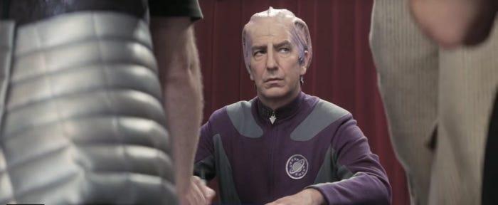"""Fotka z filmu Galaxy Quest, v němž Alan Rickman ztvárnil postavu herce Alexandra Danea, jenž ve fiktivním sci-fi seriálu hraje postavu """"Dr. Lazaruse"""". Na fotce je oblečen v kostýmu a podepisuje se fanouškům na conu. V popředí vidíme částečně 2 fanoušky zezadu. Postava Alexandra Danea je uprostřed v pozadí a se znechuceným výrazem se podepisuje."""