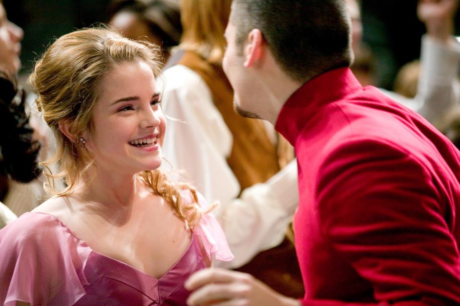 Hermiona v růžových šatech a Krum na plese. Hermiona se usmívá na Kruma v červené uniformě, kterého vidíme spíše zezadu.