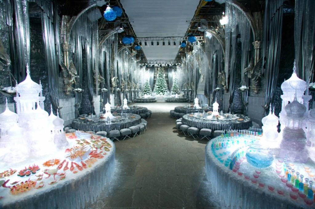 Liduprázdná Velká síň, vyzdobená k vánočnímu plesu (led, rampouchy, vánoční stromky v čele síně) a kulaté stoly plné jídla a pití všeho druhu v různých barvách.