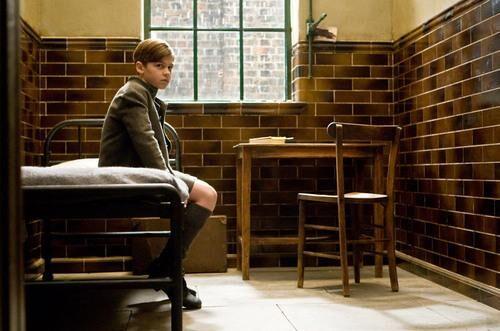 Záběr na malého Toma, který sedí na vojenské posteli v malé místnůstce, obložené hnědými kachličkami. V pravém rohu je jednoduchý dřevěný stůl s dřevěnou židlí.
