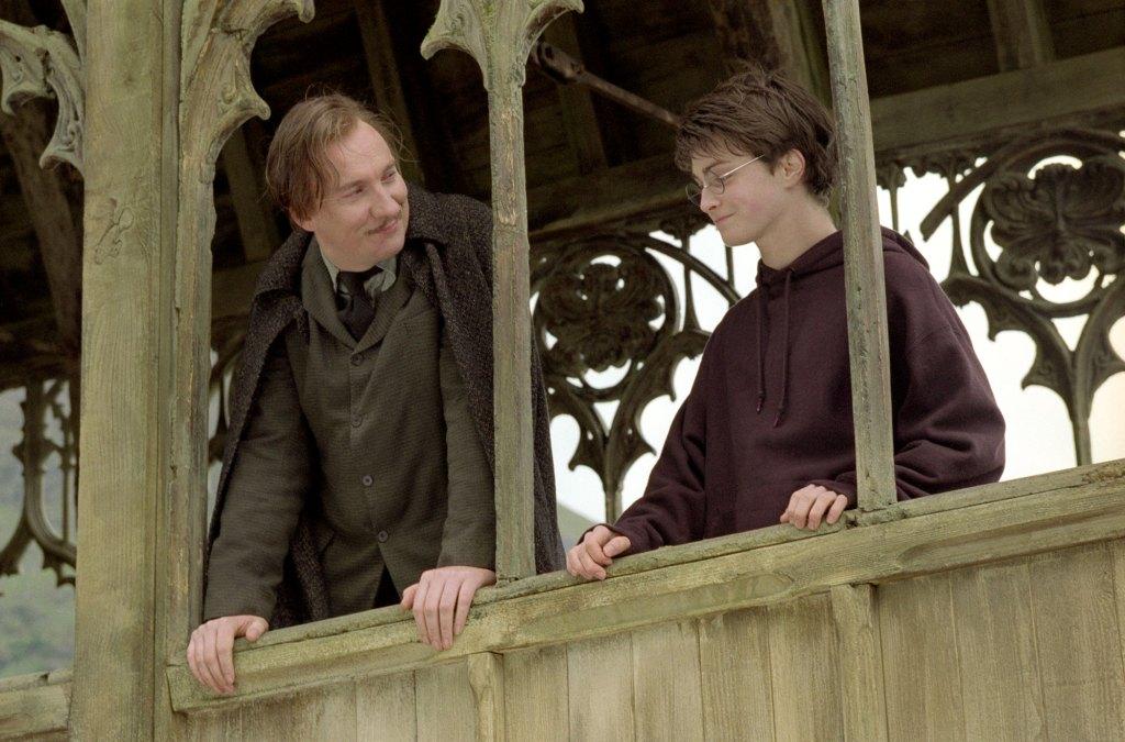 Scéna na mostě, kdy Harry (vpravo) ve vínové mikině konverzuje společně s Lupinem (vpravo) v hnědém obleku. Oba se mírně usmívají - Lupin na Harryho a Harry se dívá dolů z mostu.