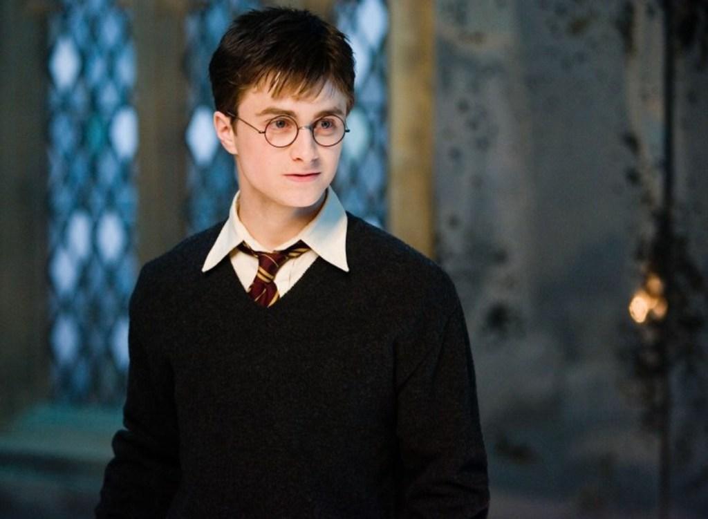 Na fotografii je horní polovina těla Harryho ve školní uniformě bez hábitu. Za ním je okno.