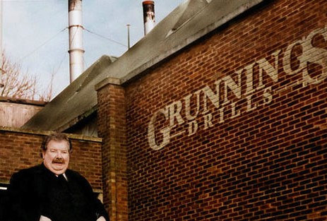 """Fotografie filmového (kníratého) strýce Vernona. Vernon je v levém dolním rohu, má blažený výraz a je oblečen v černém saku. Fotografii vévodí cihlová stěna, na níž je napsáno """"Grunnings drills"""" (vrtačky Grunnings). Fotografie byla užita ve filmech jako jeden z obrázků/fotek nad krbem v domě Dursleyů."""