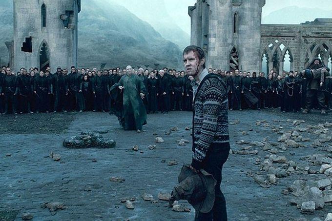 Fotografie z filmu Harry Potter a Relikvie smrti 2. část. Neville čelí Voldemortovi a jeho armádě Smrtijedů poté, co Voldemort přijde s Hagridem, který nese (zdánlivě mrtvého) Harryho. Neville má krvavou ránu na hlavě, ale v tváři odhodlaný výraz, s nímž se obrací k divákovi.