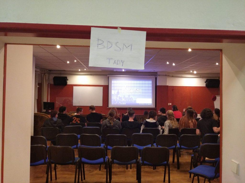 """Na fotografii je přednáškový sál. Je vidět interaktivní tabule s logem Potterfanu a před ním židličky. První tři řady jsou zabrané diváky. Na vrcholu dveří vidí papír s nápisem """"BDSM TADY."""""""
