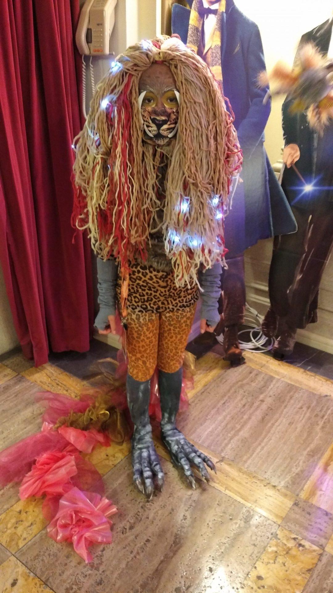 Fotografie z Potterfestu 2021 s cosplayerkou v roli hřivouna, má hřívě podobnou paruku, namalovanou horní část obličeje, přes spodní část obličeje má roušku s tygřím čenichem, leopardí sukýnku a punčochy a na nohou má drápy. Má také ocas s mašlemi.