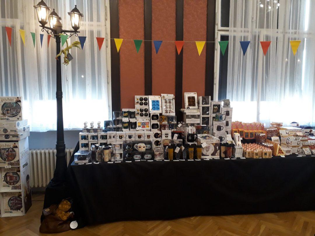Fotografie z Potterfestu 2021 ukazující stůl plný zboží v Pottershopu. Lze vidět různé hrníčky a nádoby, sladkosti aopd. Výzdobu dotváří funkční trojramenná lampa, na níž jsou zavěšeny provázky s praporky kolejních barev. Z jednoho z nich visí plyšový kůrolez.