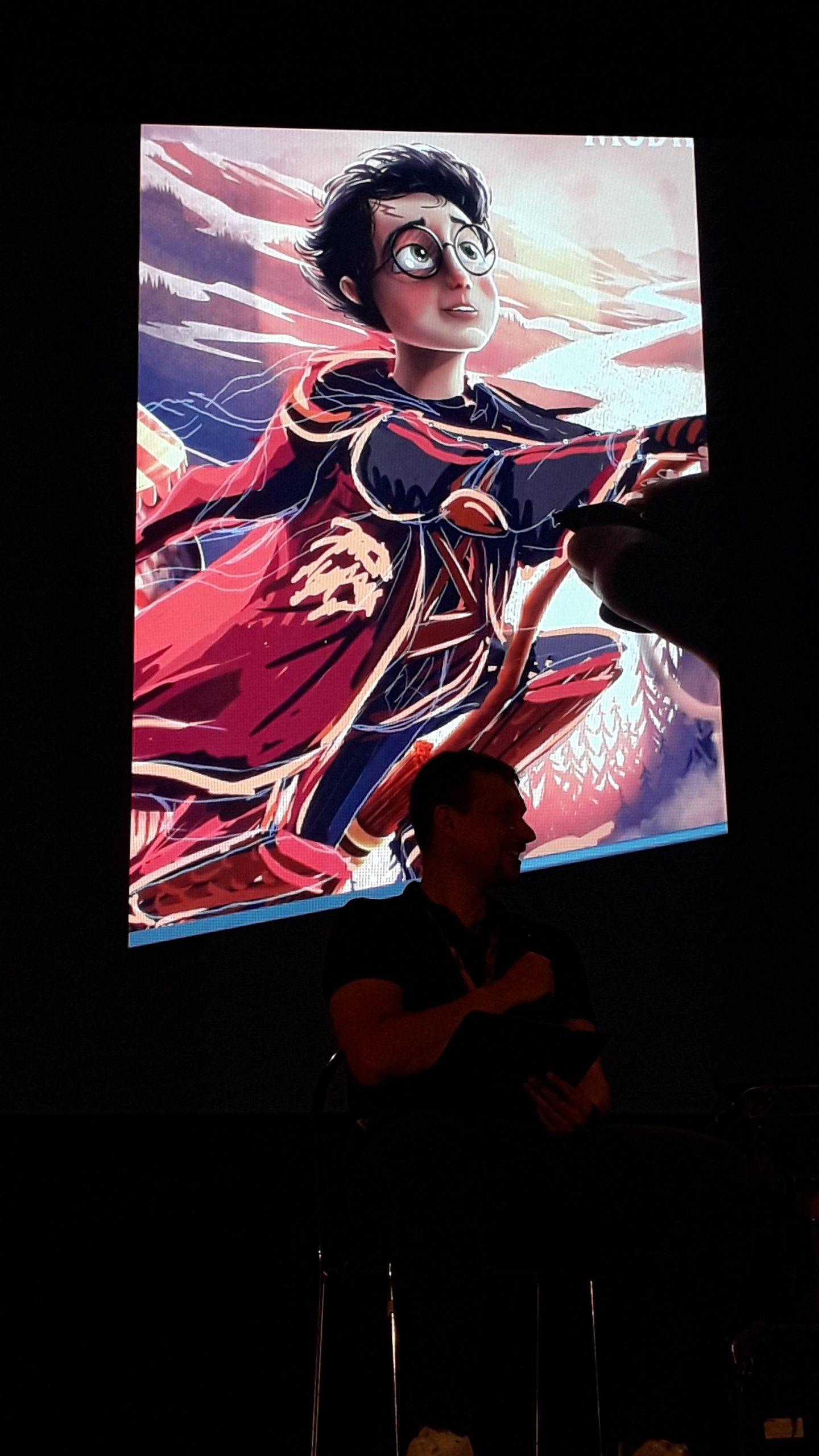 Fotografie z Potterfestu 2021 z besedy s Adrianem Machem, na níž je Thomas s mikrofonem a na obrazovce za ním vidíme Machovu kresbu Harryho letícího na koštěti.