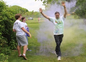 Doug Swinehart, of Pottstown, goes through a cloud of color with his hands raised during a color run fundraiser at West-Mont Christian Academy Saturday.