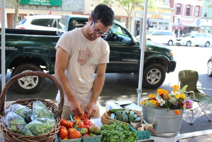 "Nathan Hasler-brooks of Tine & Toil Farm sells fresh produce and flowers during the outdoor farmers market in Pottstown last week. The market is open along High Street every Thursday from 4 to 8 p.m. until October. This week's theme for the market is ""Christmas in July."""