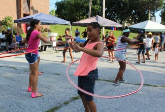 Girls have fun competing in a hula hoop contest during a Back to School Community Blockbuster at the Ricketts Center in Pottstown.