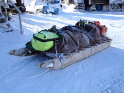 A large qamutik loaded with equipment and supplies for a winter camp
