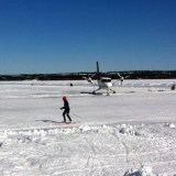 The plane moving to the deplaning area while someone cross-country skis by !