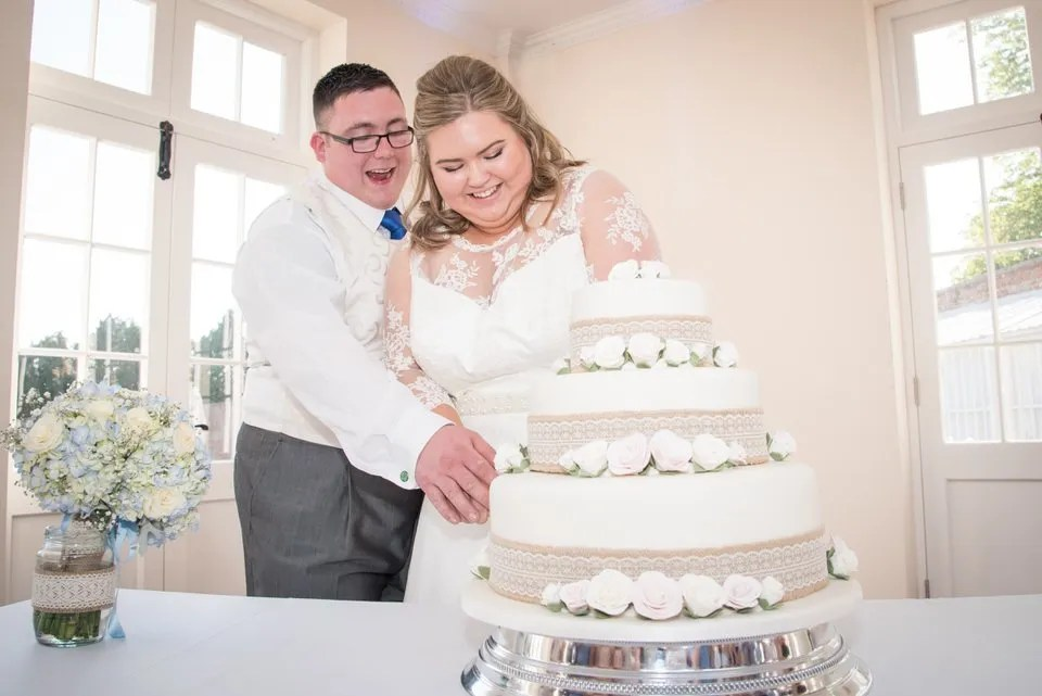 Cutting the wedding cake at Orchardleigh Estate in Somerset