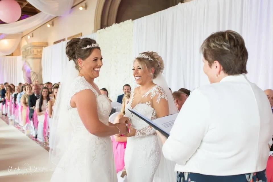 Brides laugh during wedding ceremony