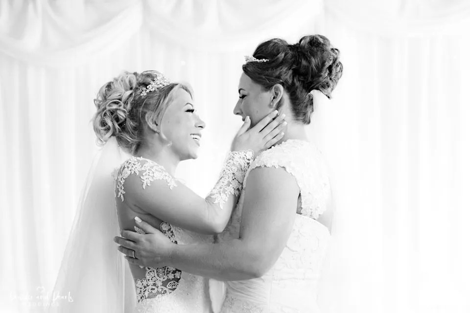 Brides kiss at their wedding ceremony