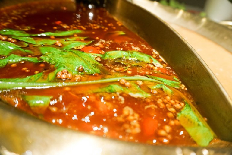 image of spicy hot pot broth with basil and peppercorn