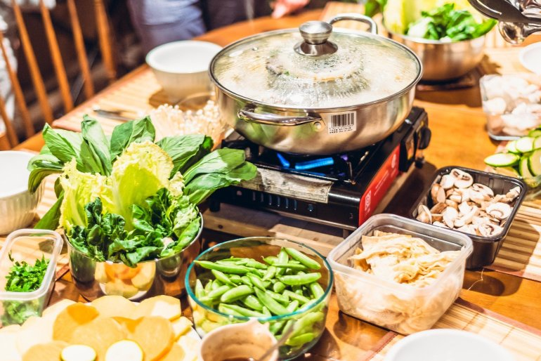 image of hot pot on hibachi burner with raw vegetables on dining table