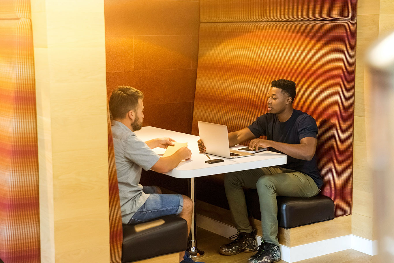Two men sit in a booth discussing technology