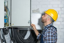 man in yellow hardhat and plaid shirt looking at control panel