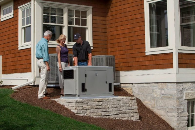 three people standing around a residential standby generator