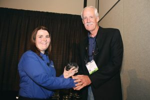 Bob Althoff of A.D. Farrow Co. Harley-Davidson in Ohio accepts the Power 50 No. 5 dealer award from Liz Keener.