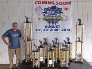 """ Chuck Decker, president and owner of the AMSOIL World Championship Derby Track in Eagle River, Wis., is shown with the huge eagle trophies to be presented at the inaugural UTV/ATV World Championship Derby. The tallest is 6 feet."