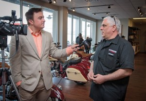 """Gotham Motorcycles owner Mark Crescitelli takes care of media duties during the grand opening."