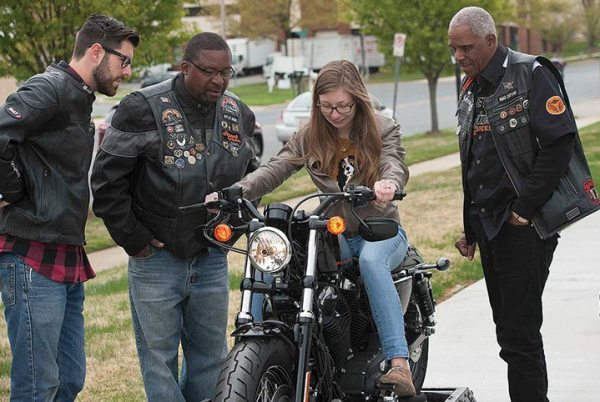 Members of Battley Harley-Davidson's local HOG chapter show a potential rider how to shift gears on the Jumpstart simulator.