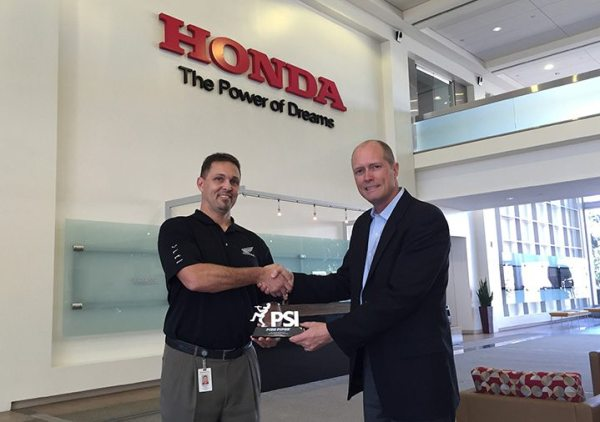 Michael Rizner, left, Honda's manager of Motorcycle Dealer Network Development and Administration, accepts Pied Piper's 2016 PSI-ILE trophy from Pied Piper president and CEO Fran O'Hagan.